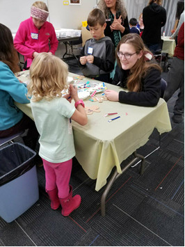 Karoline Tyne helping kid build gingerbread house